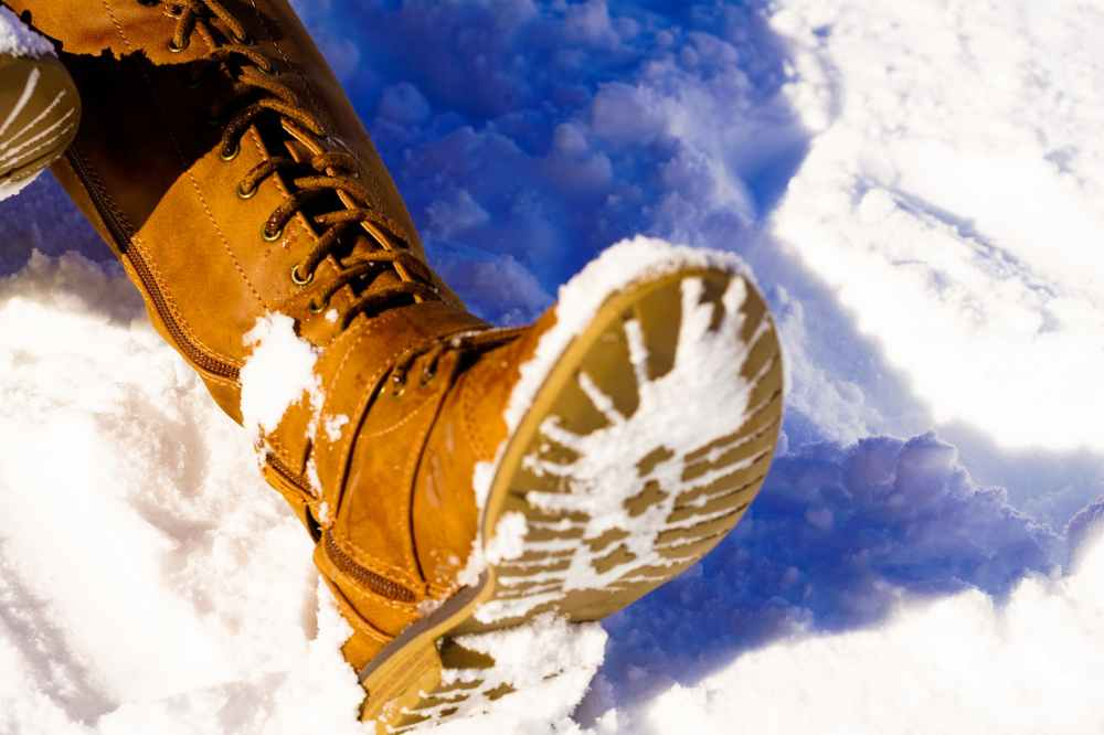 person s left foot on snowfield