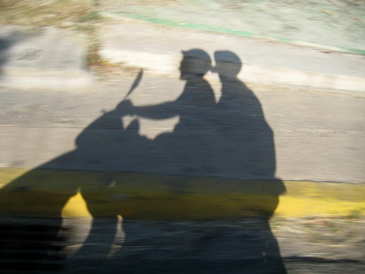 shadow image of two people on a scooter